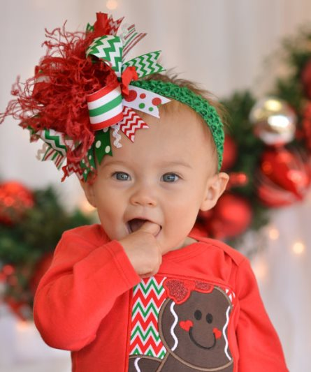 A flaxen-haired baby angel has gold-rimmed wings and wears a lavender dress. She has a gold halo above her head and she holds a shiny pink Christmas ornament tied to the end of a branch of a Christmas tree. Beside the woman, there is a Christmas tree decorated with candy canes and blue bows. Christmas Present. This is an image of a.